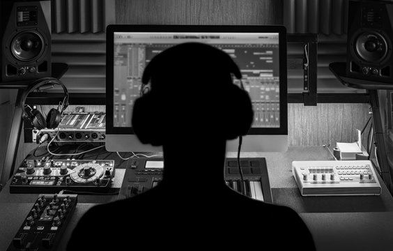 Man produce electronic music in project home studio. Silhouette. Black and white photo.