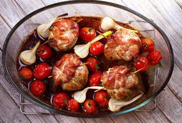 Pork rolls with cherry tomatoes and garlic. View from above, top studio shot