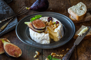 Camembert cheese with fresh figs, walnuts, raisins and honey. Rustic retro vintage ambiance.