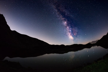 The outstanding beauty of the Milky Way arc and the starry sky reflected on lake at high altitude on the Italian Alps, Torino Province. Fisheye scenic distortion and 180 degree view.