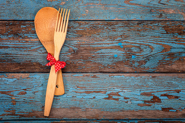 Spoon and fork on a wooden background.