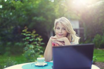 Красивая женщина сидит за столом в саду с ноутбуком и мобильным телефоном