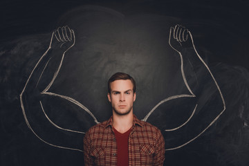 Young serious man  with drawn strong and muscled arms