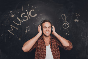 Happy smiling young man listening music in headphones