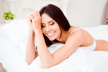 Happy pretty woman  lying on  white bed and dreaming