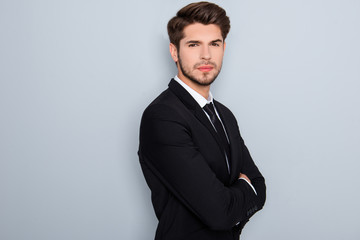 Confident serious successful businessman in suit with crossed  h