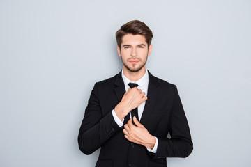Portrait of handsome businessman correcting tie on gray backgrou