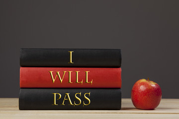Three books on a school desk with a red apple