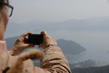 Old woman take a photo and sightseeing at Mireuksan Mountain viewpoint,South Korea,focus at camara