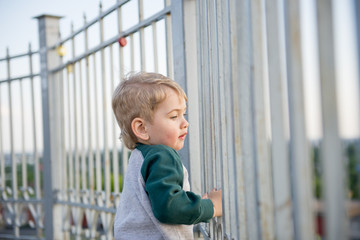 little boy climbed up on the fence