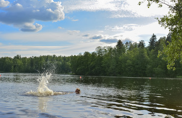 Woman swimming in a lake in summer in Finland