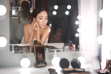 Beautiful Chinese woman applying makeup in front of camera