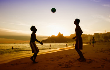 Two guys loves playing soccer at beach at Rio de Janeiro