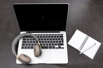 Laptop on a desk with headphones and a notepad