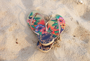 Colorful flipflop on the white sand beach