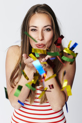 Party girl blowing confetti at camera