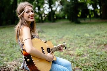 Beautiful hippie girl playing guitar