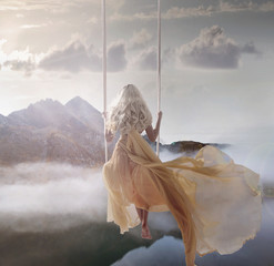 Aluminium Prints Artist KB Attractive lady sitting on the swing above the calm lake
