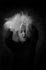 Sexy young woman putting hands in her disheveled hair. Sexy look in black and white portrait. Screeming woman with messy hair.