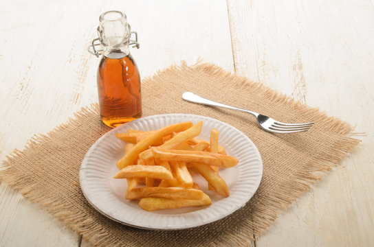 french fries on a paper plate and malt vinegar