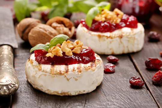 Grilled cheese with cranberry jam and walnuts on old wooden back