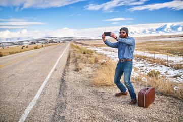 bearded hipster hitch hiker taking selfie beside empty road in n