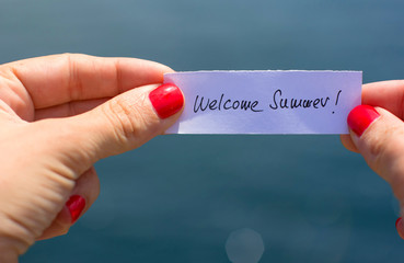 Welcome Summer contept. Woman hands holding a piece of paper wit