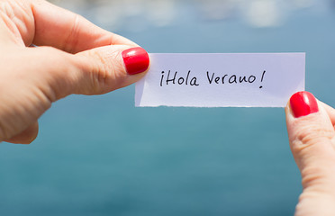 Woman holding a piece of paper saying Hello Summer in spanish. H