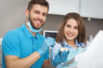 Dentist explaining to female patient how to brush her teeth.