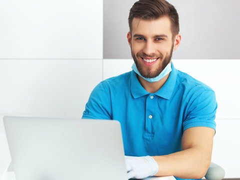Young male dentist working with notebook.