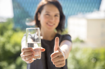 Young woman holding a glass of water recommend drinking water with thumb up