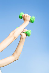 Woman's hand holding dumbbells outdoor in summer. Close up, concept of healthy and sport