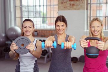 drei frauen trainieren mit gewichten