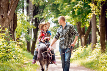 Beautiful little girl on a pony with his father.