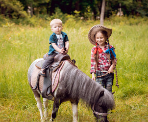 Beautiful girl with little brother on a pony.