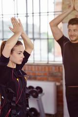 frau macht ein ems-workout im studio mit einem trainer