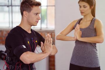 mann und trainerin beim ems-workout im studio