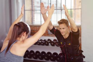 trainerin und sportler beim ems-workout im studio