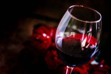 Red wine and red roses, black background, selective focus