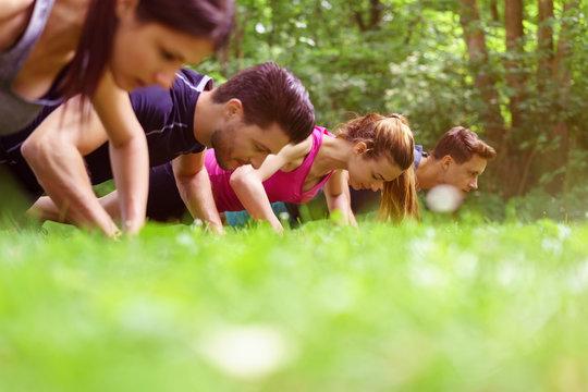 sportler machen liegestütz auf einer wiese im park
