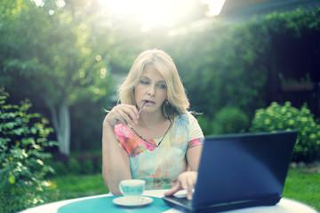 Красивая блондинка пьет кофе и смотрит в ноутбук за столом в саду
