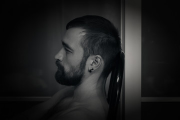 portrait of a man in profile closeup. Brutal macho with a beard. Black and white photography, dark style