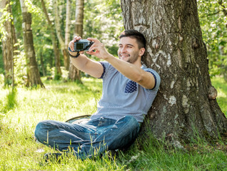 Portrait of young hipster man with camera outdoors. Young male photographer making selfie on summer day.