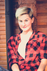 Fashionable portrait of a young beautiful woman in red lumberjack shirt, jeans, white t-shirt and sneakers. Trendy blonde hipster girl having fun on a terrace of a rich wooden house on a sunny day.