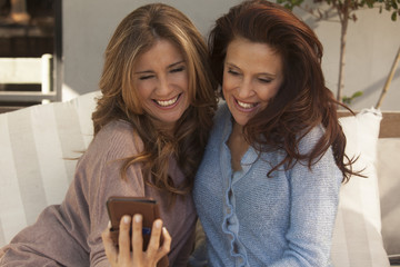 Happy adult women smiling with mobile phone outdoors