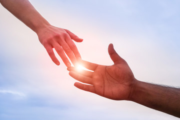 Black and white hand reaching - Handshake of different skin color hands united against racism and racial problems - Concept of human aid to migrant and refugees