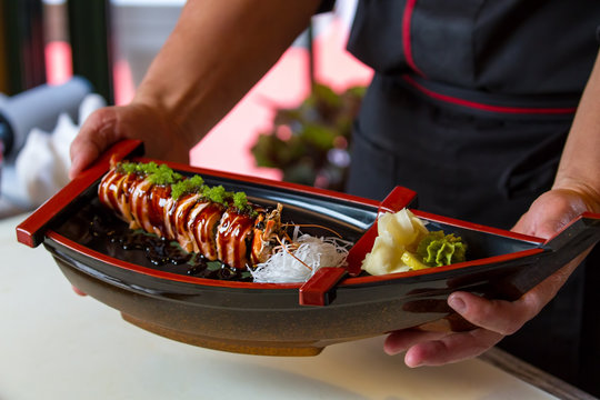 Man's hands hold sushi boat. Sushi rolls with green spice. Uramaki rolls and wasabi. Special offer at sushi cafe.