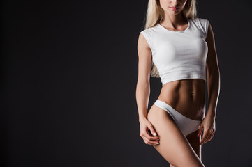 Perfect body of a young athletic girl on dark background