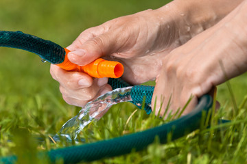 hands of gardener connecting hoses for irrigation, closeup