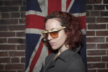 Portrait of young woman standing against British flag